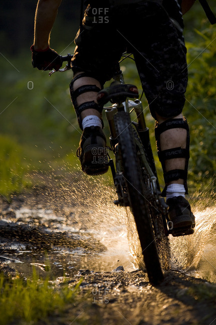 A mountain biker riding though a sunlit puddle on Idaho Peak in New Denver, British Columbia, Canada