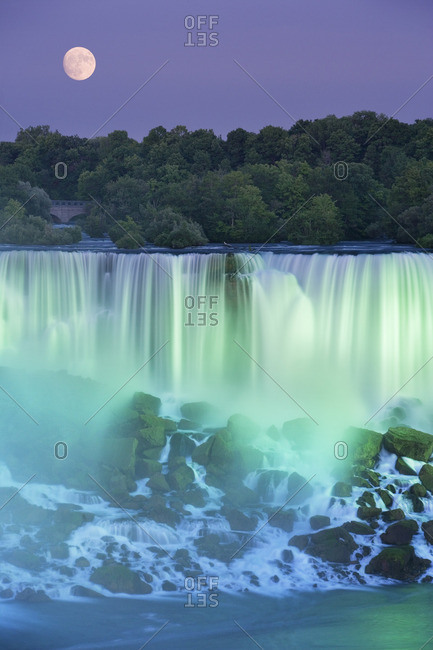 The American Falls with Full moon at dusk lit with lights photographed from Niagara Falls, Ontario, Canada