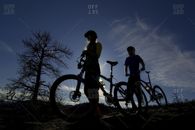 Silhouette of a couple stopping to take in the view while mountain biking near Kamloops, British Columbia, Canada