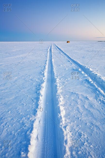 Vehicle tracks leading out to an Ice Fishing Shack on frozen Lake Winnipeg, near town of Gimli, Manitoba, Canada