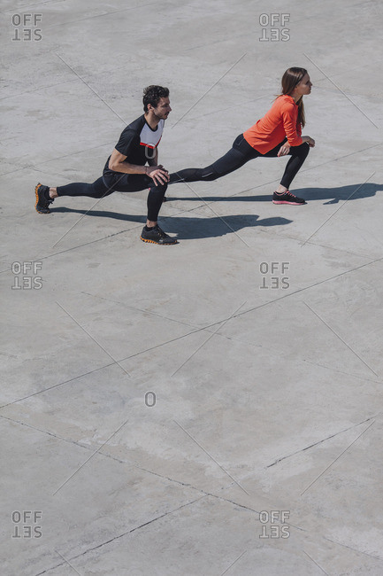High angle view of friends stretching legs in public square during sunny day
