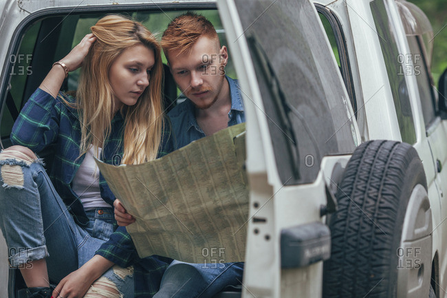 Couple analyzing map while sitting in off-road vehicle at forest