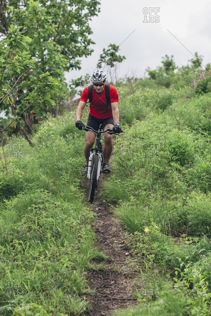 Mountain biker riding on pathway amidst grass on hill