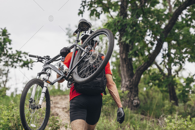 Rear view of man carrying mountain bike up hill