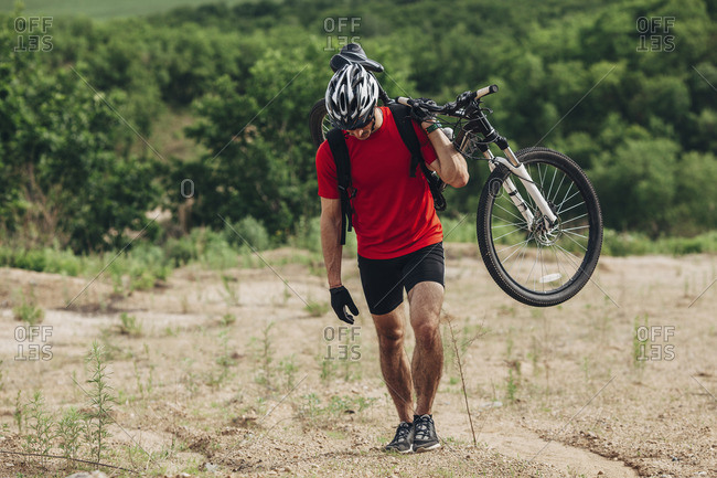 Determined man carrying mountain bike up hill