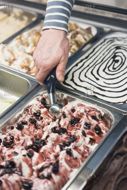 Detail of hand scooping ice cream from container at store