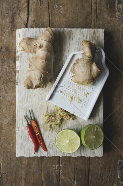 High angle view of ginger, lime and chili with grater and cutting board on table