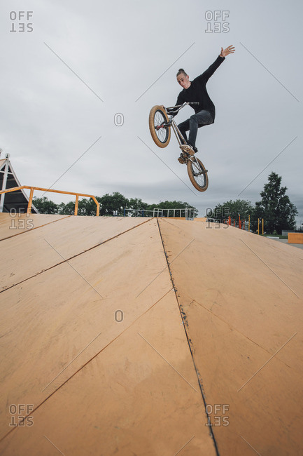Teenager performing stunt on BMX bicycle at skateboard park