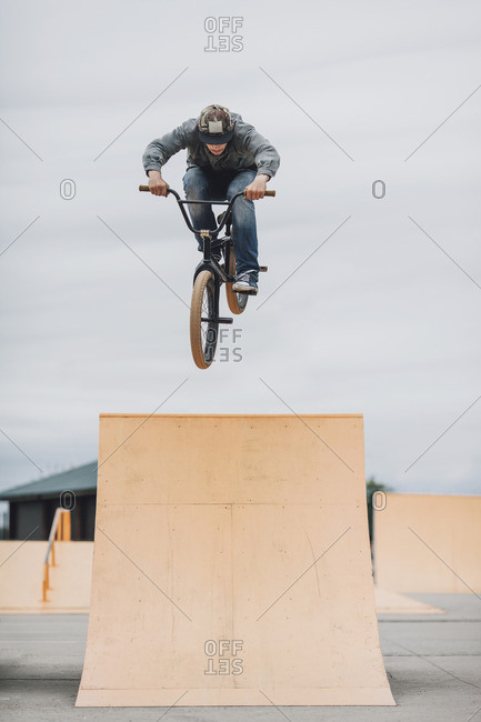 Teenager performing stunt on ramp at skateboard park