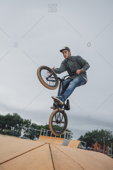 Teenager performing stunt at skateboard park against sky
