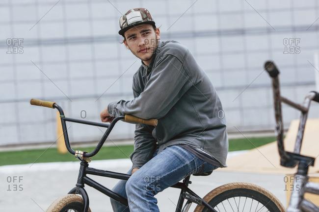 Thoughtful teenage boy sitting on bicycle at skateboard park