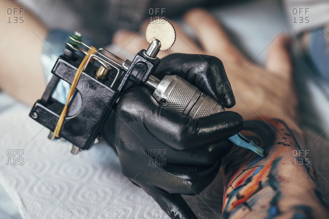 Cropped image of artist tattooing design on human hand
