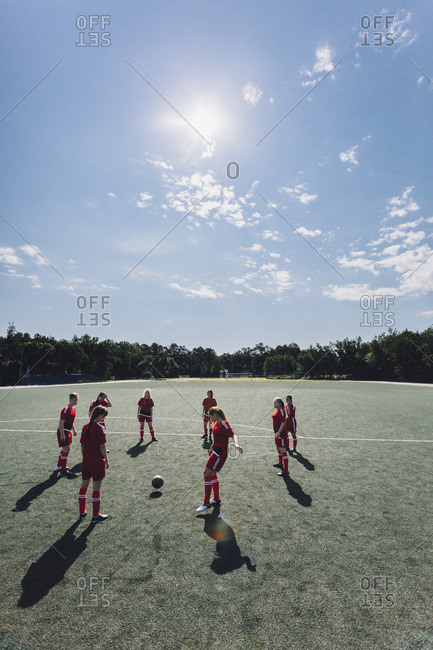 High angle view of team playing soccer on field during sunny day