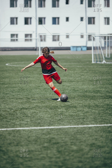 Determined teenager kicking ball on soccer field
