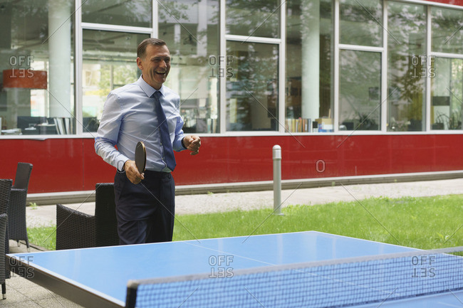 Cheerful businessman playing table tennis at creative office