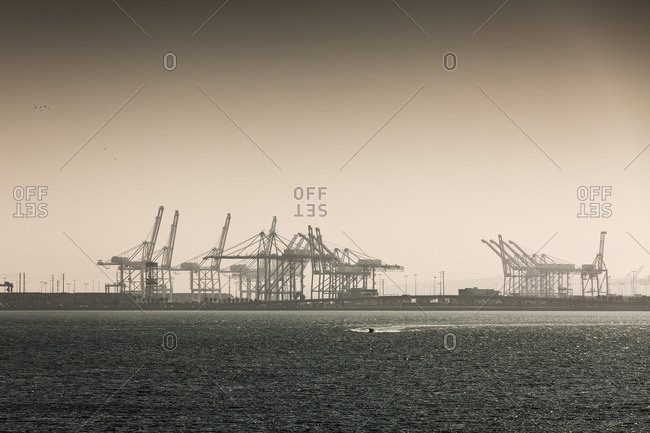 Sea in front of cranes at port against clear sky, Long Beach, California, USA