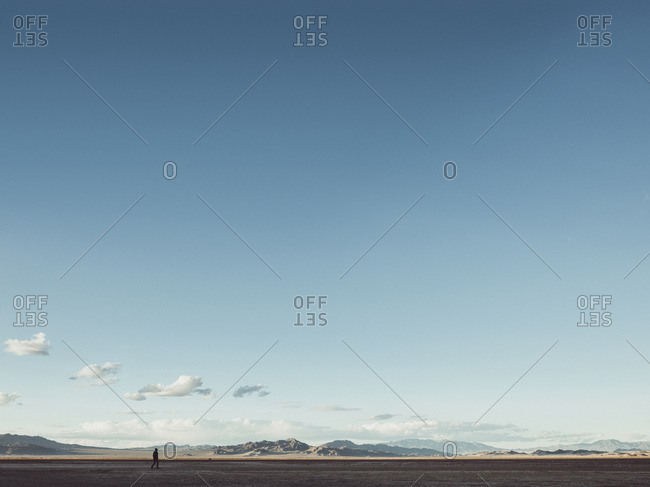 Distant view of man walking on field by mountains against sky, California, USA