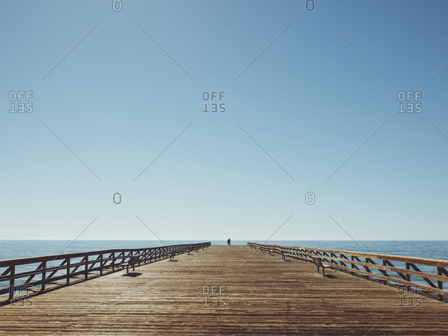Pier over sea against clear blue sky