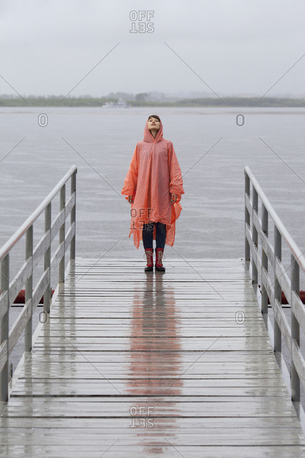 Woman wearing raincoat standing on jetty during rainy season