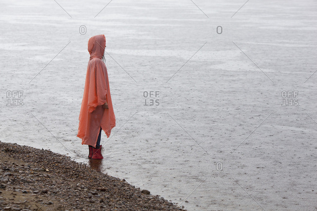 Woman wearing raincoat standing at lakeshore during rainy season
