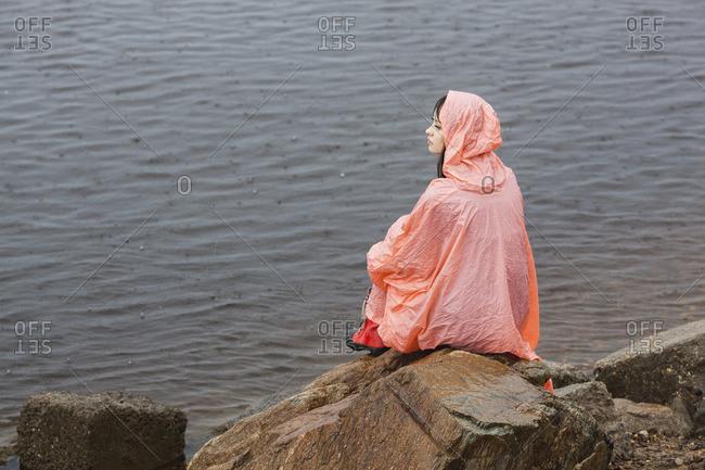 Thoughtful woman wearing raincoat sitting on rock at lakeshore during rainy season