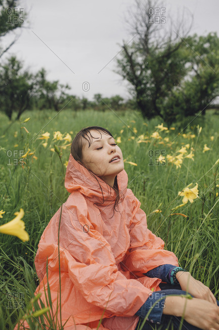 Young woman relaxing amidst yellow flowering plants during rainy season