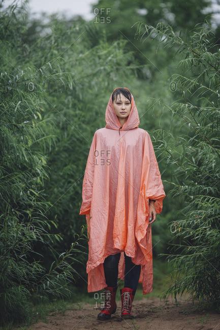 Portrait of woman wearing raincoat standing amidst plants during rainy season