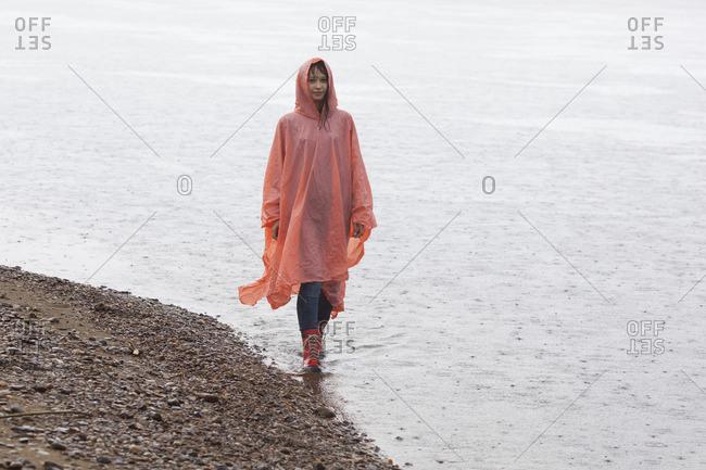 Woman wearing raincoat walking at lakeshore during rainy season
