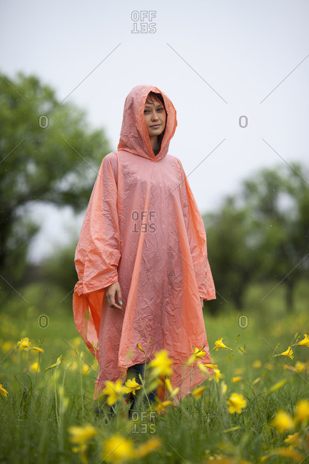 Woman wearing raincoat standing amidst yellow flowering plants in rainy season