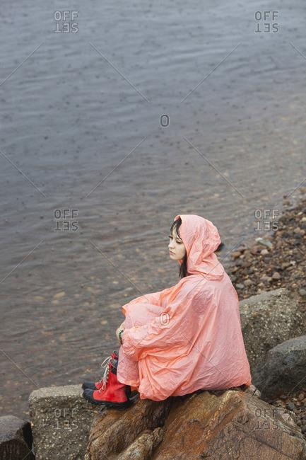 Thoughtful woman wearing raincoat sitting on rock at lakeshore in rainy season
