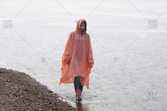Woman wearing raincoat walking at lakeshore in rainy season