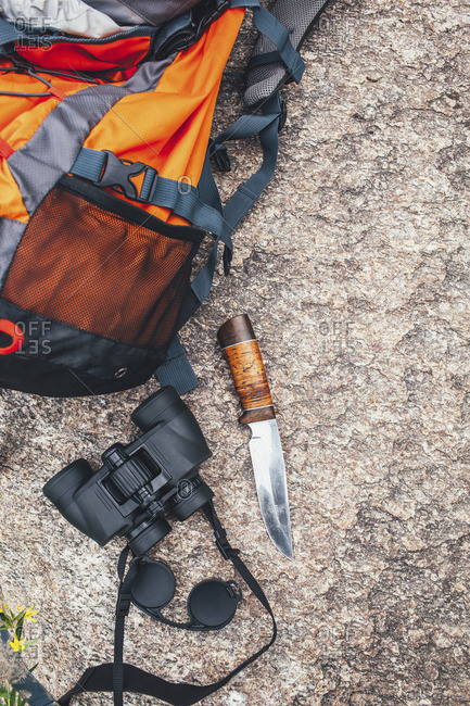 High angle view of backpack with binoculars and knife on rock