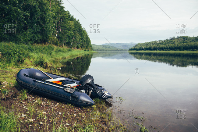 Inflatable motorboat moored at riverbank in forest against sky