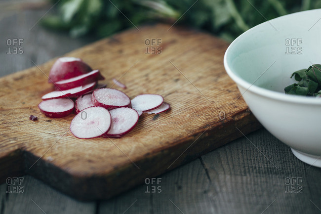 Close-up of radish slices on cutting board by bowl at table