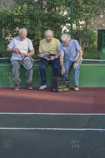 Senior friends with tennis rackets sitting against fence at playing field