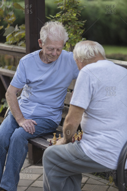 Senior friends playing chess on park bench