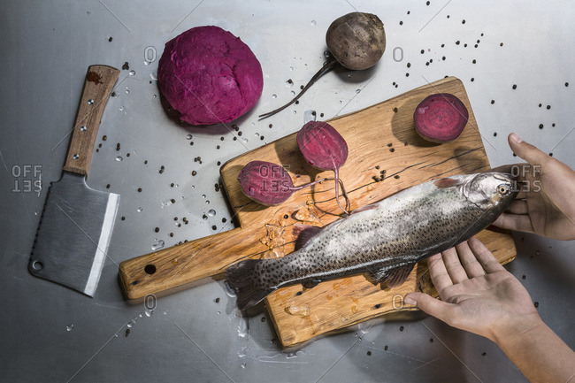 Cropped image of hand holding fish with beets at table