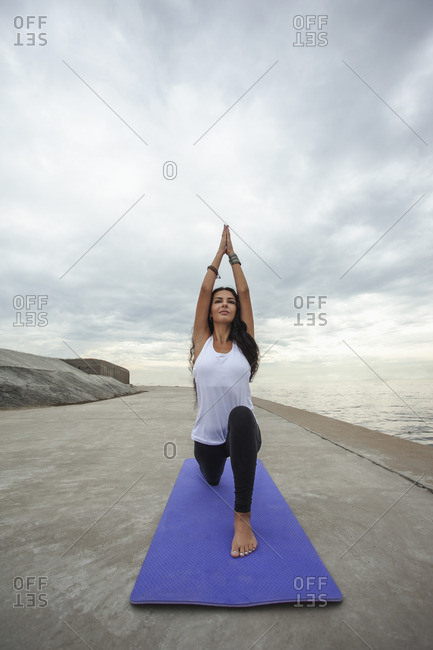 Young woman practicing Warrior 1 yoga pose at beach