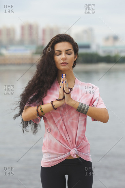 Young woman with closed eyes practicing yoga in prayer position against river