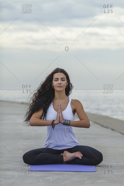 Woman with closed eyes practicing yoga in prayer position at beach against cloudy sky