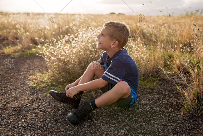 Young boy sitting in a field at dusk
