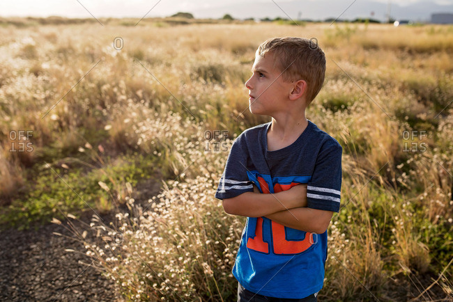 Young boy stands with his arms crossed in field at dusk