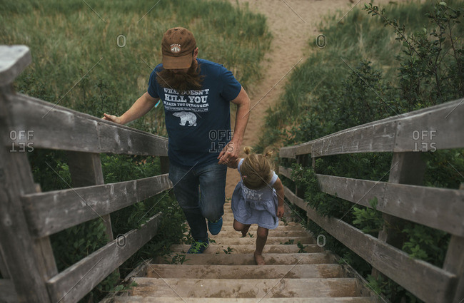 Father and daughter walking up stairs from beach