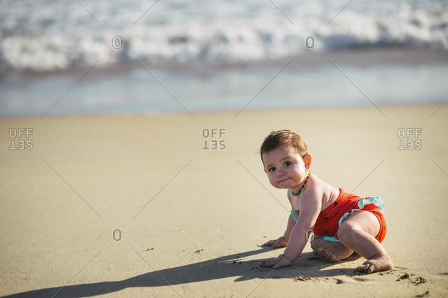 Toddler girl crawling around a beach