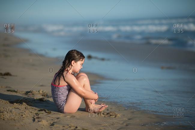 Girl sitting alone on a beach
