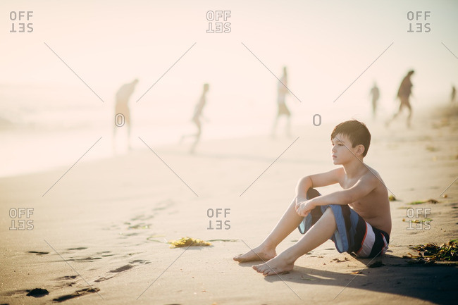 Boy staring off sitting on beach