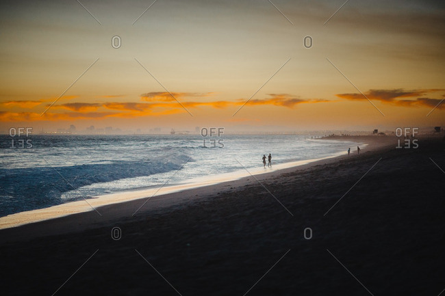 People strolling in tranquil beach sunset