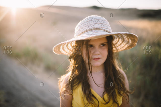 Girl in sun hat in rural field