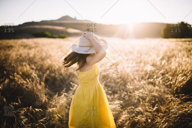 Girl holding hat in sun dappled field