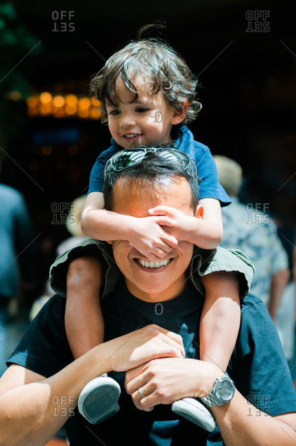 Boy covering man's eyes while on shoulders